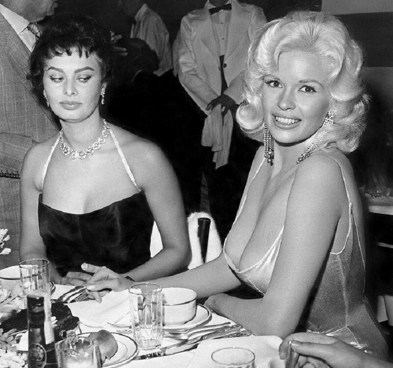 Sophia Loren i Jayne Mansfield podczas przyjęcia Sophia Loren wyjaśniła, co się naprawdę stało, gdy zrobiono to zdjęcie. Kiedy przysiadła się do niej Jayne Mansfield, Loren skupiła swój wzrok na jej biuście. - Obawiałam się, że zaraz znajdzie się on na moim talerzu - stwierdziła.
